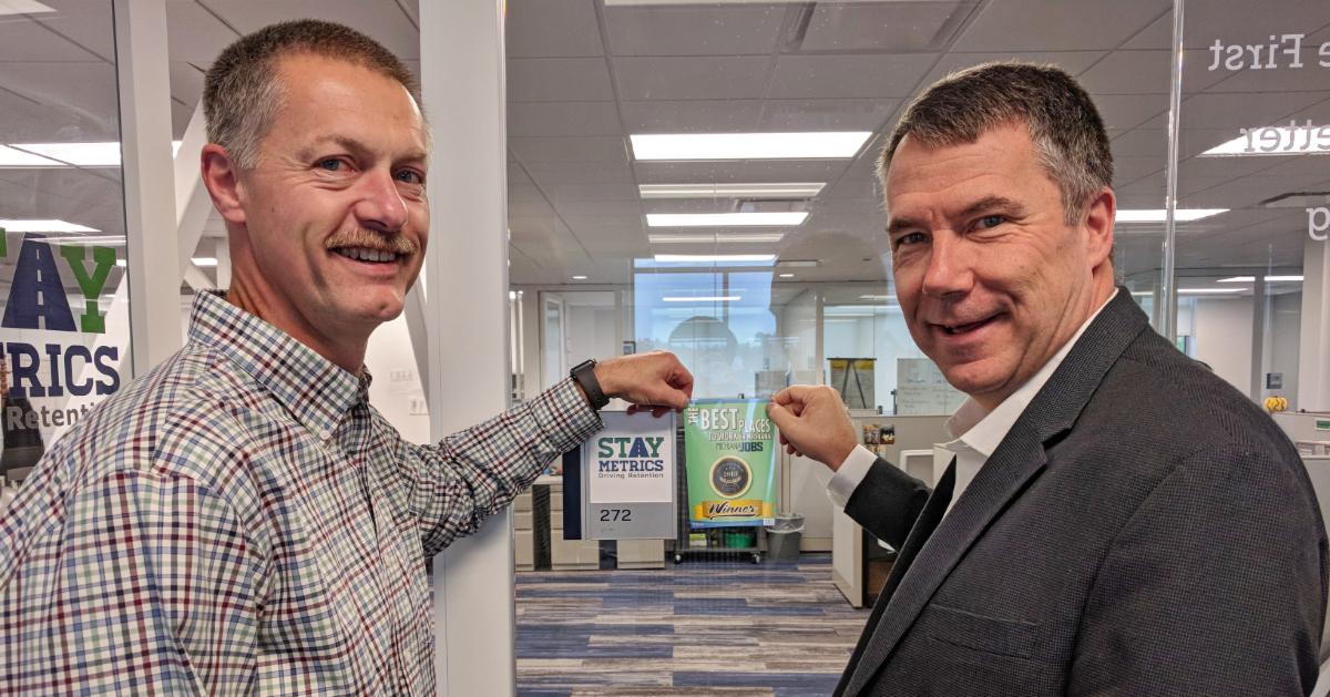 Tim and Kurt affix Best Places to Work logo